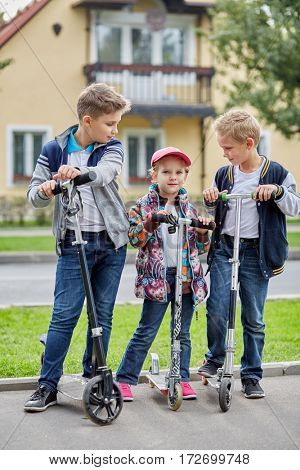 Two boys look at girl standing with push scooters on road against two-storied house.