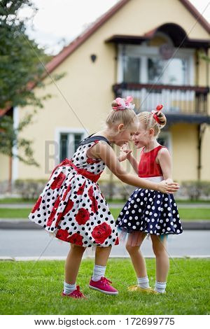 Two girls in polka-dotted dresses dance on grassy lawn against two-storied house.