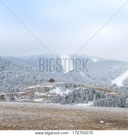 Beautiful white snowy winter in foggy mountains landscape