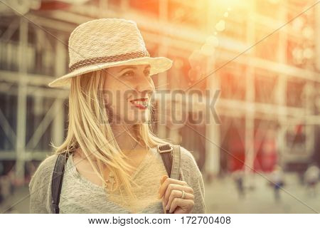 Womans portrait. Young female in hat stay on the street in downtown Paris City  under sunlight at day time.