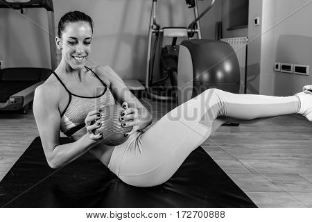 Young woman exercising in the gym, black and white