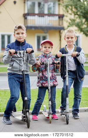 Two boys and girl stand with push scooters on road against two-storied house.