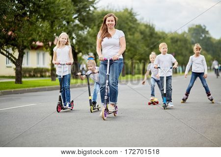 Woman and five children on scooters, roller skates and skateboard ride on street .