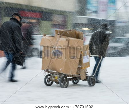 Poor man pulling a cart with cardboard in the city. Intentional motion blur