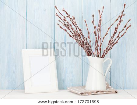 Pussy willow bunch and blank photo frame with copy space on shelf in front of wooden wall