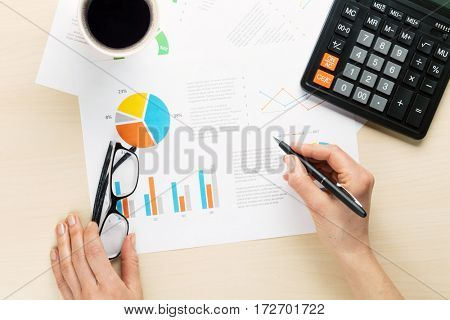 Woman working with reports and charts over wooden office desk. Top view