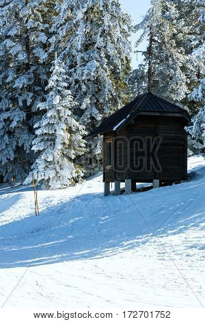 Log cabin shelter is among snow covered pines in the winter mountains at wonderful sunny day