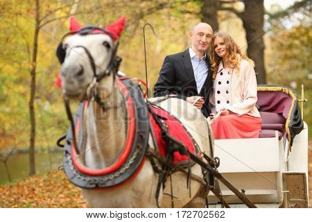 Man and woman sit in coach with horse and hold reins in autumn park
