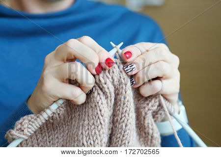 Hands of knitting woman in blue dress, close up view, noface