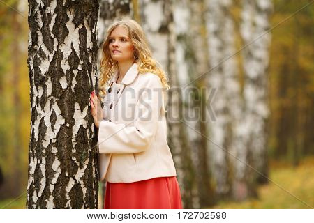 Beautiful young woman in red skirt poses near birch in yellow autumn park