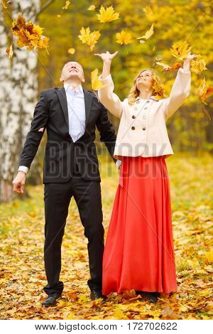 Beautiful woman and man throw up leaves in yellow autumn park