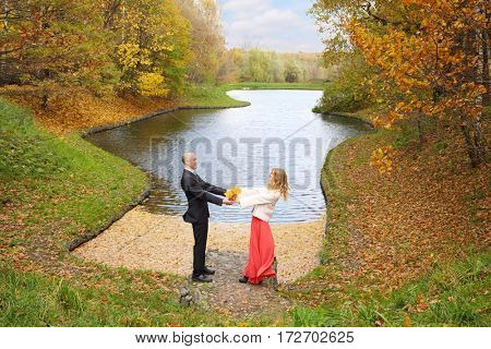 Happy man and young woman pose near pond in yellow autumn park