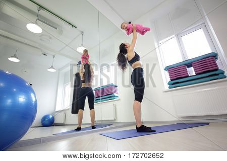 Mother in sportswear raises the little baby near the mirror in the gym