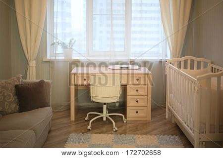 Interior room with a desk with scales for newborns by the window, a sofa and a baby cot