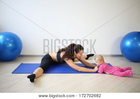 Smiling woman sitting on the splits leaned forward to the baby lying on stomach in the gym