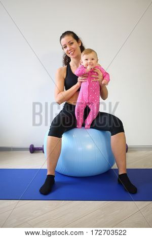 Happy mother with baby sitting on the big blue ball in the gym