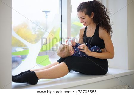 Woman gives to drink water baby on the windowsill in the gym