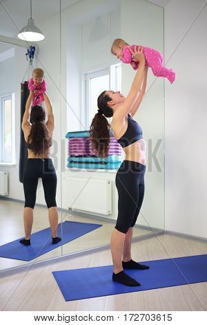 Mother in sportswear standing picks up little baby near the mirror in the gym