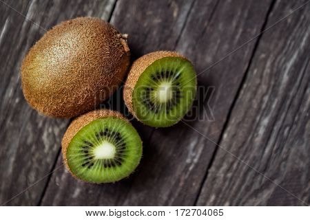 Green fresh kiwi fruit cut on pile of kiwis