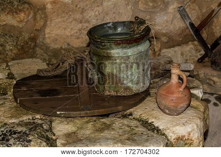 The Old iron bucket and the clay jug on the ancient stone water well in Nazareth Village Israel. Ancient Holy Land