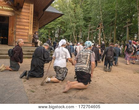 Grabarka Poland - August 14 2016: Pilgrims of the Orthodox Church moving on knees around the church on the Holy Mount of Grabarka.
