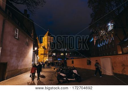 STRASBOURG FRANCE - DEC 6 2015: View from Rue de la Monnaie street to the church of St. Thomas eglise Saint-Thomas Thomaskirche in central Strabourg with people walking toward the curch and to the Petite France