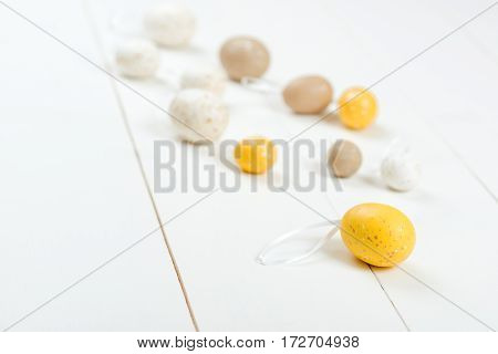 Easter card. Scattered pastel Easter eggs on the wooden background. Selective focus.