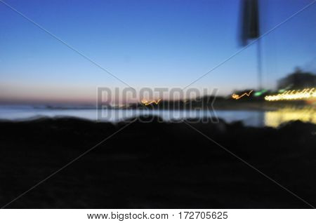 blurred background. sunset on the beach. twilight. the horizon line. the lights on the coast