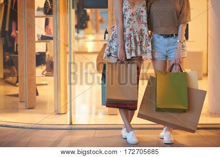 Cropped image of girls with paper bags standing at showcase