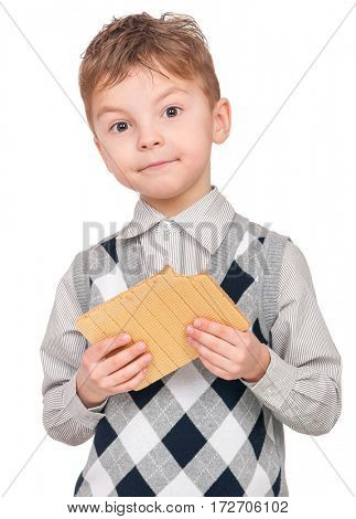 Portrait of happy little boy eating waffle isolated on white background. Child looking at camera.