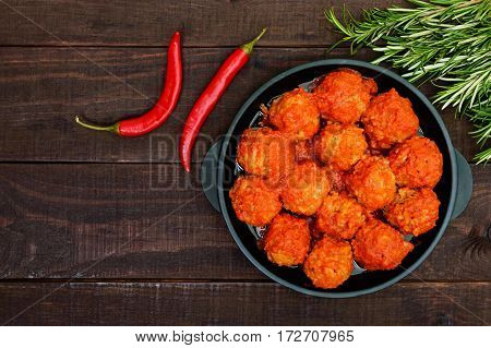 Meat balls in spicy tomato sauce served on a cast iron pan on a dark wooden background. The top view.