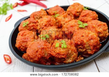 Meat balls in spicy tomato sauce served on a cast iron pan on a white wooden background. Close up