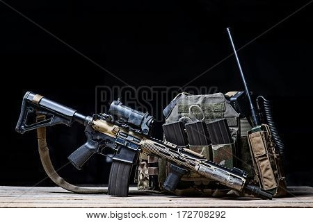 Assault rifle with sight,bulletproof vest,ammo and radio on dark background