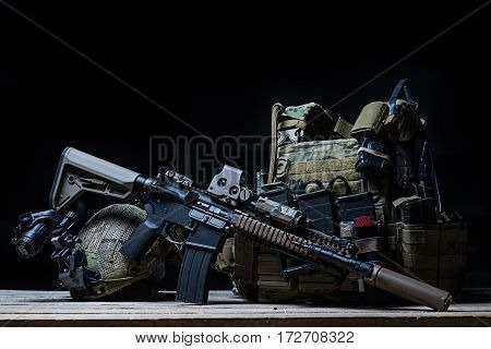 Assault rifle with silencer,bulletproof vest,helmet with night vision device on dark background