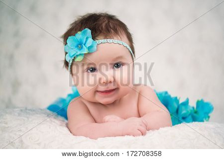 Newborn portrait of a girl with a bandage knitting a blue flower.