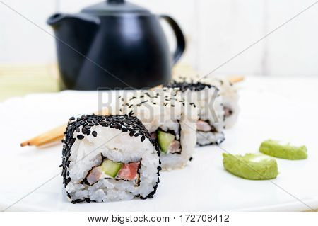 Traditional eastern dish with salmon shrimp - sushi rolls on a white plate. Close-up.