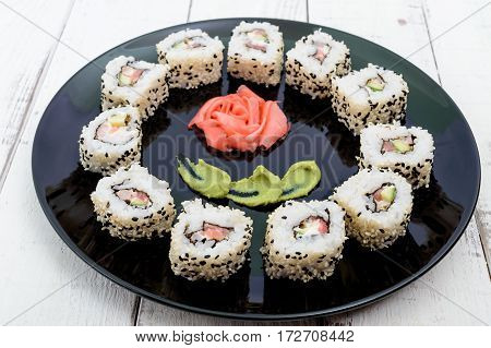 Traditional eastern dish with salmon shrimp - sushi rolls on a black plate. Close-up.