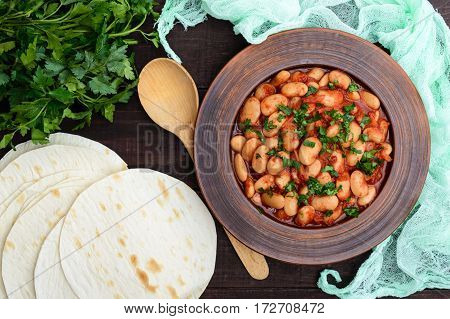 White large beans in sweet and sour tomato sauce in a clay bowl on a dark background. The top view. Vegetarian cuisine. Lenten meal.