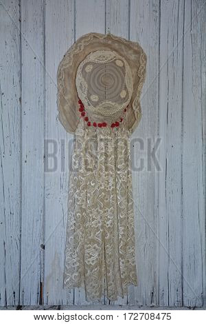 Old lady's hat from point with pearls hangs in the middle of an old white wooden wall