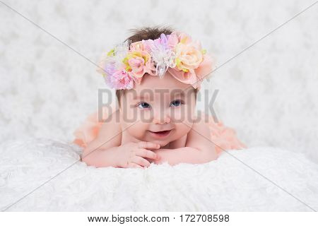 Newborn girl portrait with knitted bandage in the form of a flower