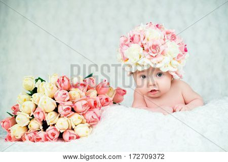 A newborn baby girl in the hat of the rose smiles. Portrait on a white background.