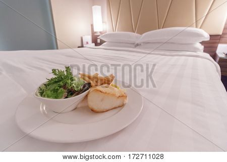 Fresh food on a bed in a hotel room, room service concept