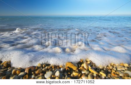 Sea wave and foam on the shore. Nature composition.