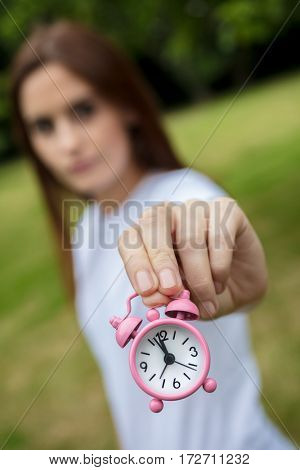 Young adult woman or girl outside holding a pink alarm clock in time running out concept photograph