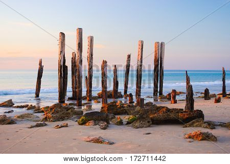 Soft pink sunset sky as a backdrop to the iconic Port Willunga jetty ruins at Port Willunga South Australia.