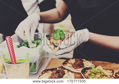 Female street vendor hands make taco outdoors. Mexican cuisine snacks, fast food of commercial kitchen.