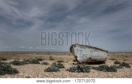 An abondoned boat on a desolate beach. Taken at Dungeness, Kent, UK
