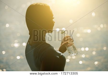Silhouette Of A Young Female Athlete In Tracksuit Drinking Water From A Bottle On The Beach In Summe