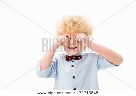 Cute curly boy rubbing his eyes on white