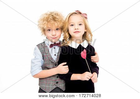 Cute little kids holding red paper heart on stick and looking at camera